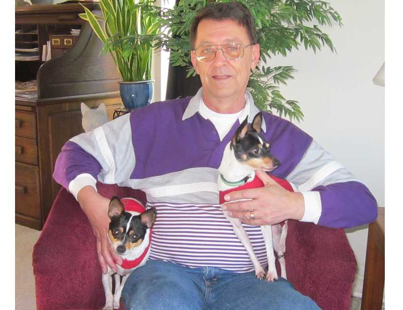 by: BARBARA SHERMAN - THEY DON'T KNOW THEY'RE DIFFERENT - Summerfield resident Paul Ochs holds Ellie (left), a rat terrier, and Maggie, an American toy fox terrier.
