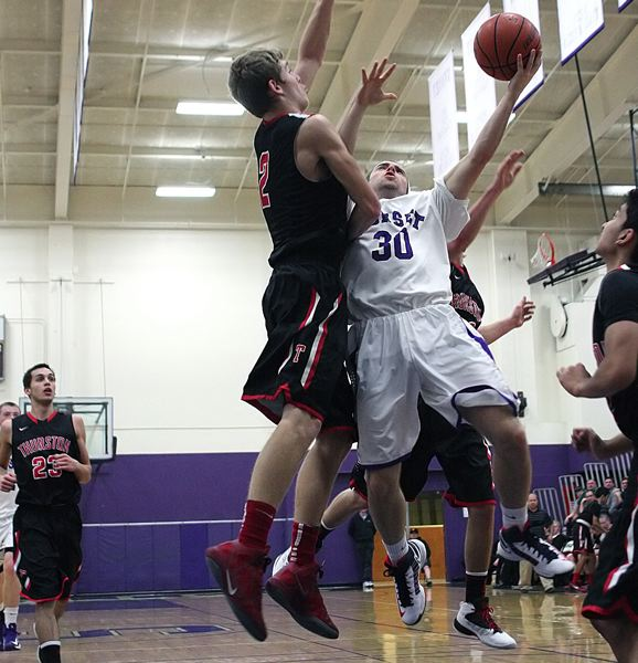 by: MILES VANCE - TO THE HOOP - Sunset senior Tucker Hutchinson tries to make a layin over Thurston's Brendin Quinn during his team's Tuesday playoff win over the Colts at Sunset High School.