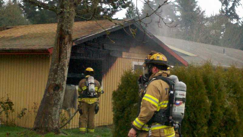 by: TUALATIN VALLEY FIRE & RESCUE - Crews examine the damage of a Tualatin home which caught fire Thursday afternoon.