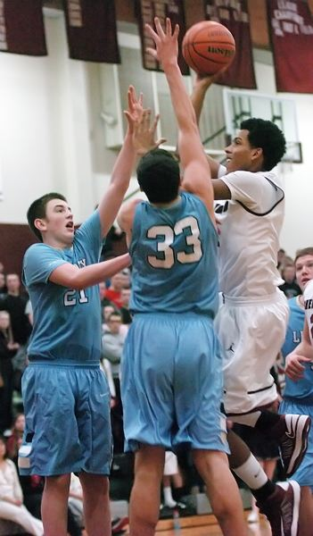by: DAN BROOD - HANDS UP -- Sherwood High School senior post Alex Jones (right) shoots over a pair of Liberty defenders in Friday's game.