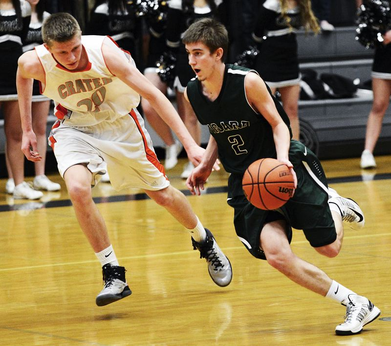 by: BRUCE BERG - DRIVING -- Tigard junior Nick Kaelin (right) looks to move up court against Crater's Connor Lane in Tuesday's playoff game. The Tigers won 62-41.