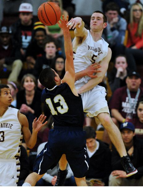 by: JOHN LARIVIERE - Milwaukie senior wing C.J. Hubbard (5) leaps high to block a shot by Marist senior guard Ben Fusek in Fridays state playoff game with the Spartans.