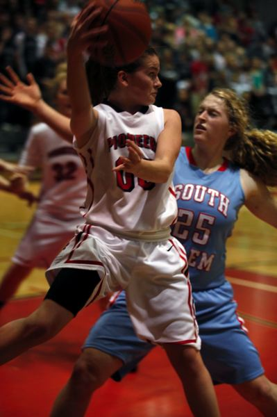 by: JONATHAN HOUSE - Oregon City senior Montana Walters serves up an assist as the Pioneers go on the attack in Saturdays 60-42 win over South Salem.