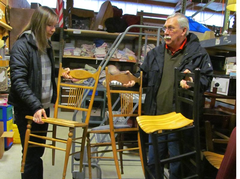 by: PHOTO BY ELLEN SPITALERI - Amy Graves and her father, Lee Roundtree, moves chairs around in the Open Arms and Helping Hands warehouse.