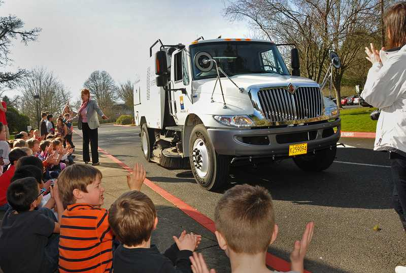 by: VERN UYETAKE - Oak Creek Elementary School students applaud as city employees demonstrate the newest street sweeper.