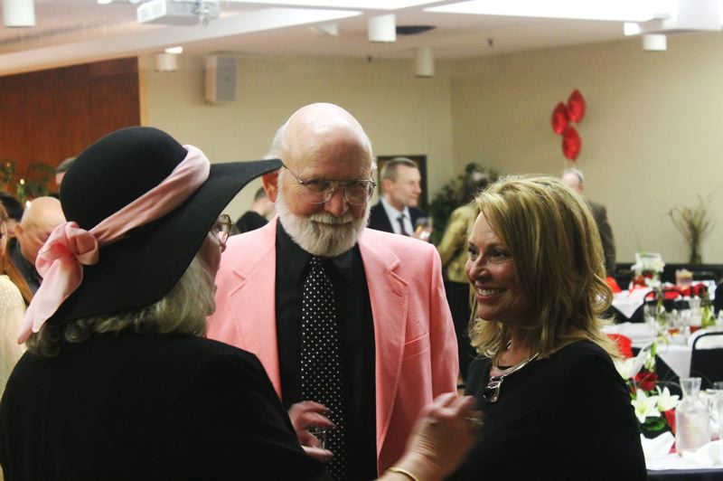 by: NEWS-TIMES PHOTO: JOHN SCHRAG - Karyn Rainone, of Cornerstone Management Group, chats with with Jill and Barry Wilson after the conclusion of the live auction Saturday evening.