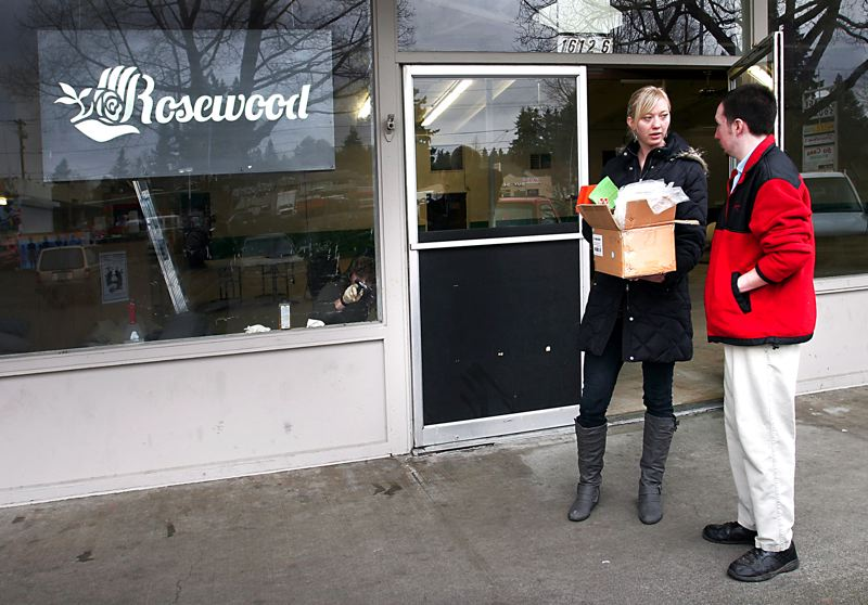 by: OUTLOOK PHOTO: JIM CLARK - Jenny Glass, Rosewood Initiative executive director, receives a box of certificates from Chris Lord, manager of the nearby Papa's Pizza. The certificates will be used for free mini pizzas, lunch buffets and cookies for volunteers.
