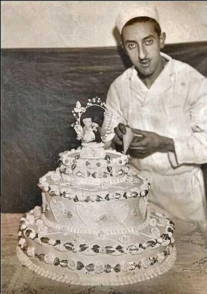 by: COURTESY OF BARBARA PORCO - Santo Porco in his early years as a baker, with one of his signature cakes.