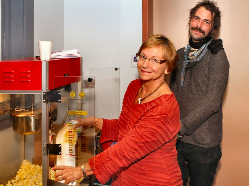 by: DAVID F. ASHTON - CMC Board member Carolyn Landsverk, and her son - a former CMC musical student, Joe Landsverk - scoop up fresh popcorn for guests at the first Family Friday Concert of the season.