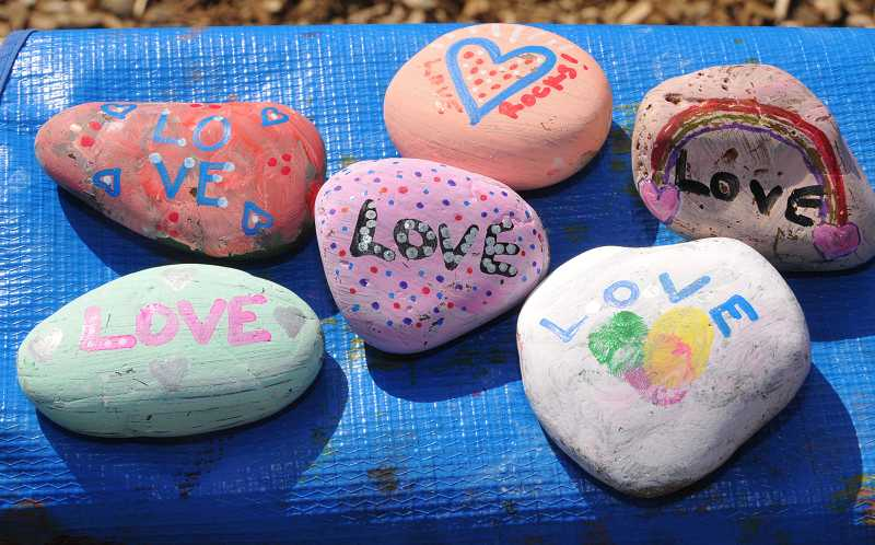 by: VERN UYETAKE - A set of completed love rocks waits to be placed around the community.
