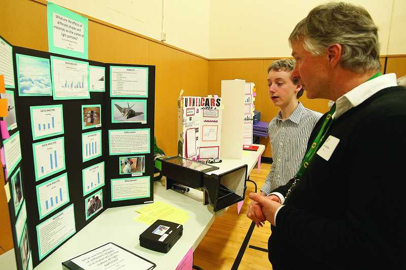 by: PAMPLIN MEDIA GROUP: JOSH KULLA - Wood Middle School eighth-grader Kjel Petterson-Willey discusses his project with CREST Director Bob Carlson.