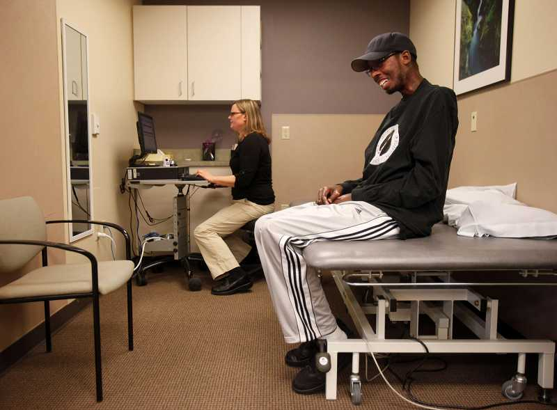 by: TIMES PHOTO: JONATHAN HOUSE - Erion Moore chats with his physical therapist Katie Carr during an office visit. 'I want to do seven days a week [of therapy] if I can. At least six,' says Moore.