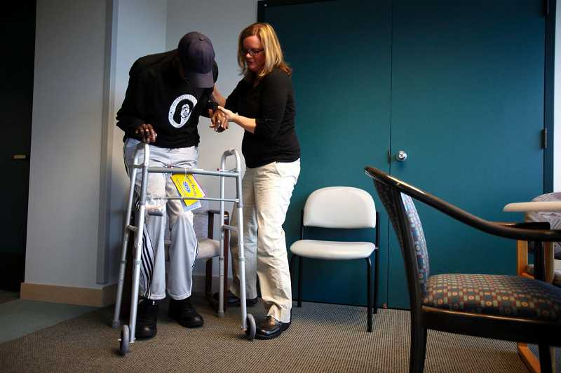 by: TIMES PHOTO: JONATHAN HOUSE - Physical therapist Katie Carr helps Erion Moore claps a walker during physical therarpy at Schools Immediate Care Clinic in Tigard.