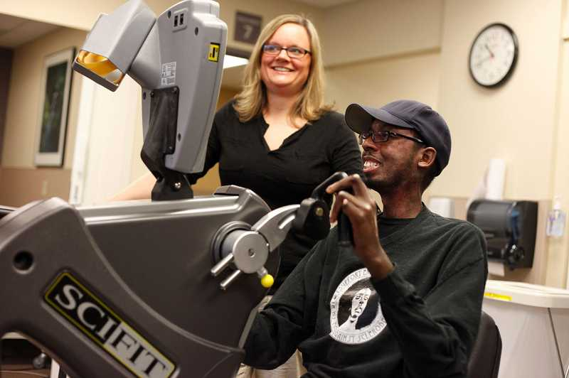 by: TIMES PHOTO: JONATHAN HOUSE -  Erion Moore works with physical therapist Katie Carr to regain strength after a stem cell transplant to help with his scleroderma, a rare disease that causes the skin to harden.