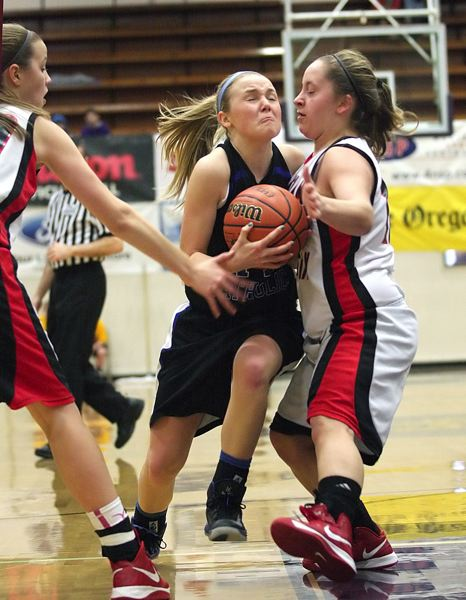 by: MILES VANCE - PUSH IT - Valley Catholic junior Lindsie LaBonte splits two Santiam Christian defenders on a drive during her team's quarterfinal win on Feb. 28 at Marshfield High School.