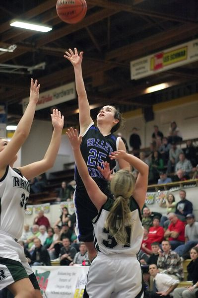 by: MILES VANCE - FLYING HIGH - Valley Catholic junior guard Grace Mannen lofts a shot over Rainier's Kylee Crape (left) and Jaden Thurston in the Valiants' Friday night semifinal win at the Class 3A state tournament at Marshfield High School in Coos Bay.