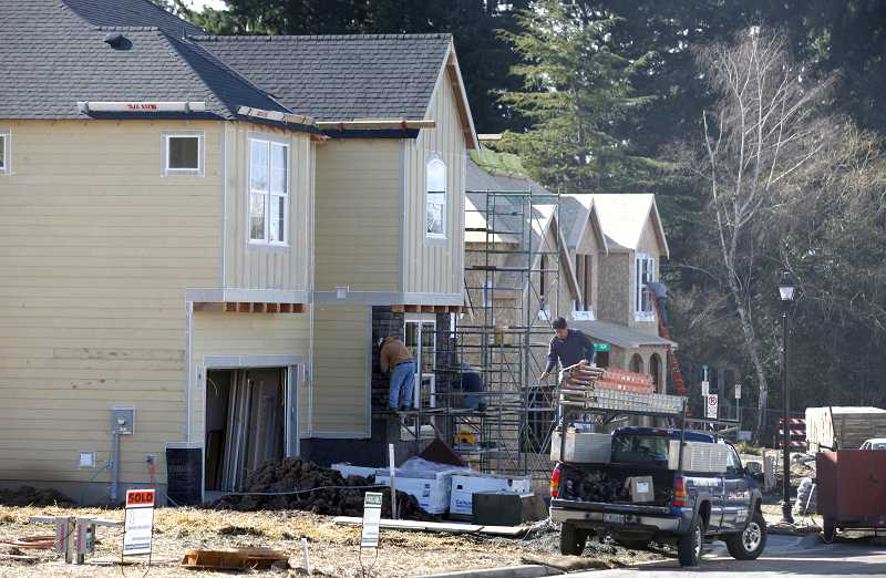 by: TIMES PHOTO: JONATHAN HOUSE - Construction workers put finishing touches on newly built homes in the Bronson Creek Farms development taking shape off West Union Road in Bethany.