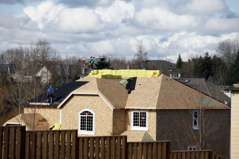 by: TIMES PHOTO: JONATHAN HOUSE - Workers affix shingles to the roof of a new home in the Bronson Creek development in Bethany.