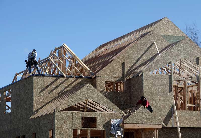 by: TIMES PHOTO: JONATHAN HOUSE - Construction workers install the roof to a new home in the Bronson Creek development.