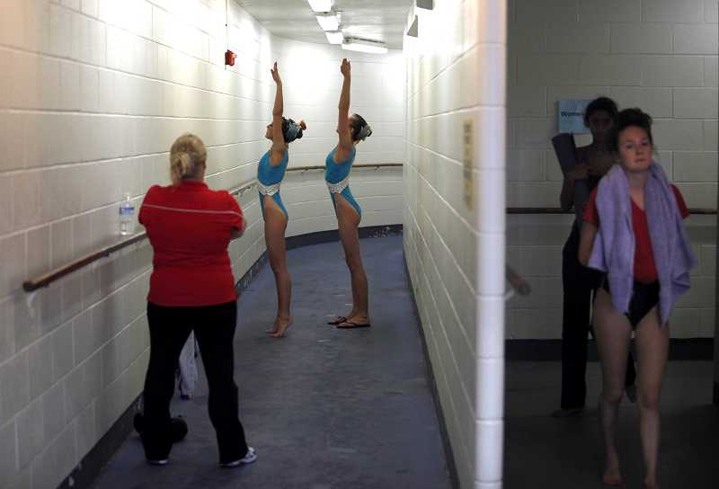 by: TIMES PHOTO: JONATHAN HOUSE - Masha Garin, left, and teammate Gracie Young practice in a bathroom hallway prior to their performance.