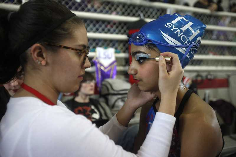by: TIMES PHOTO: JONATHAN HOUSE - Akhila Kandaswamy of Tualatin Hills Synchro gets a dab of mascara prior to her teams performance.