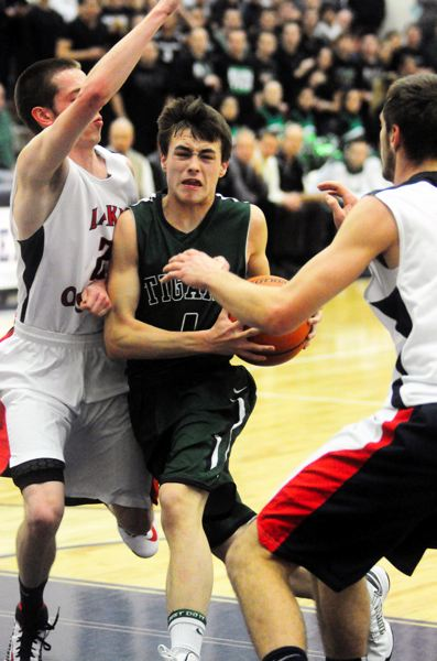 by: MATT SHERMAN - ON THE DRIVE -- Tigard High School junior Bryan Berg looks to make his way to the basket between Lake Oswego's Daniel Verburg and Calvin Hermanson in Friday's Class 6A state playoff second round game.