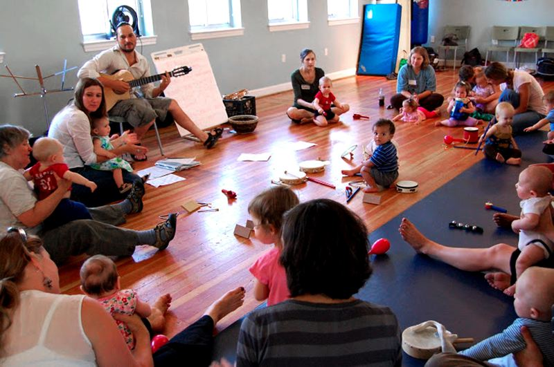 by: CONTRIBUTED PHOTO - Pablo Grabiel strums his guitar while moms encourage their children and join them, making sounds that blend with the music of the group. Grabiel will offer classes at the Sandy Community Center in April.