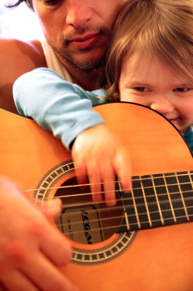 by: CONTRIBUTED PHOTO - Pablo Grabiel guides his daughter, Estela, 3, and together they create musical sounds with his guitar and peak her interest in the instrument.