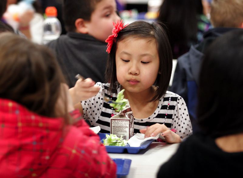 by: OUTLOOK PHOTO: JIM CLARK - Lynch Meadows Elementary School second-grader Melanie eats her lunch featuring food from a new healthy lunch program.