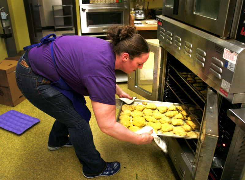 by: OUTLOOK PHOTO: JIM CLARK - Lynch Meadows Elementary kitchen manager Michelle Dryer rearranges breaded chicken pieces in the oven.