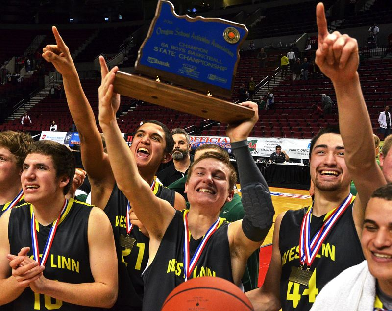 by: VERN UYETAKE - West Linn's Jarrod Howard holds the state championship trophy surrounded by his teammates in the moments following the Lions' 45-41 victory over Central Catholic Saturday night at the Rose Garden.