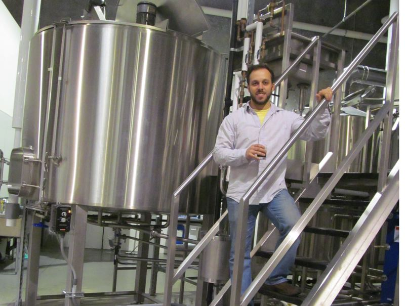 by: PHOTO BY ELLEN SPITALERI - Ben Edmunds next to a fermenter at Breakside Brewery.