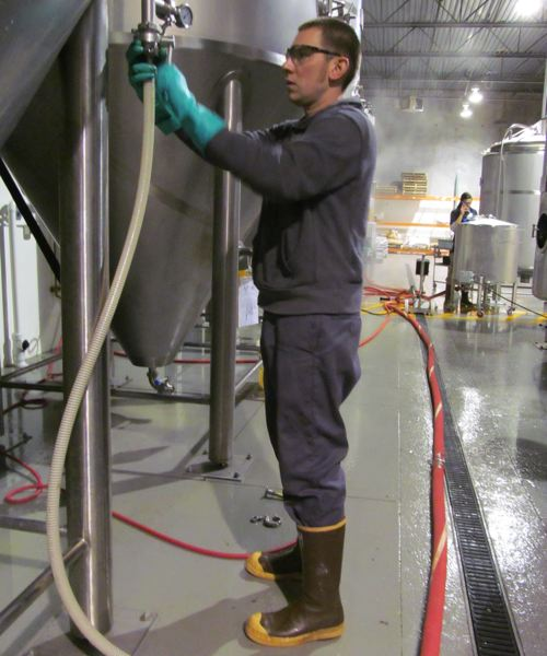 by: PHOTO BY ELLEN SPITALERI - Jacob Leonard, director of brewery operations, empties a fermenter at Breakside Brewery.