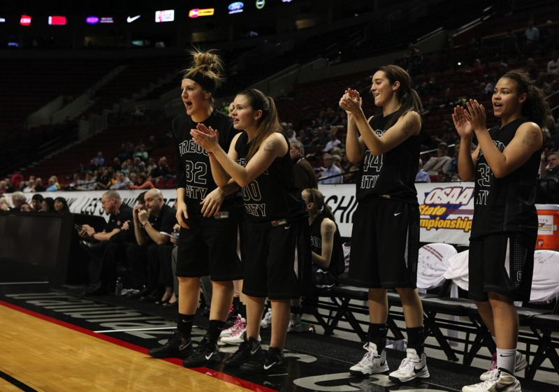 by: JAIME VALDEZ - With the game in hand, Oregon City seniors (from left) Johanna Paine, Montana Walters, Jenae Paine and Tiani Bradford applaud the play of their teammates during the Pioneers 68-29 rout of Tigard in the third-place final of the 2013 Class 6A State High School Basketball Tournament. The defense-minded Tigers entered the state tournament having allowed opponents just 30 points a game. This is the 28th consecutive season that Oregon City girls teams have won trophies at the states big-school state tournament.