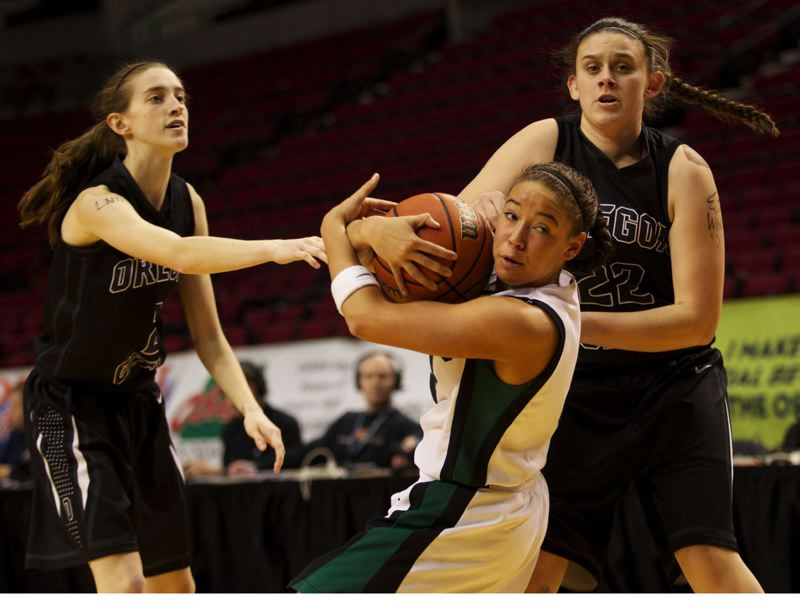 by: JAIME VALDEZ - Tigard star Lexi Carter looks for help from the officials as she is tied up by Oregon City seniors Chelsi Brewer (left) and Catelyn Preston during Saturday afternoons third-place final at the Rose Garden.