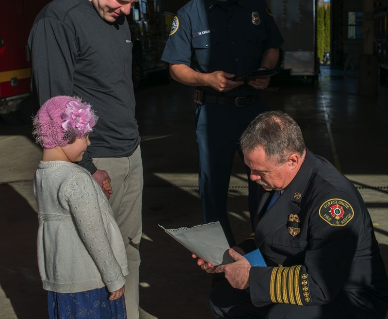 by: NEWS-TIMES PHOTO: CHASE ALLGOOD - Michael Kinkade, chief of the Forest Grove and Cornelius fire departments, accepts a Thank you picture from Faith Canfield after pinning an honorary firefighter badge on her.
