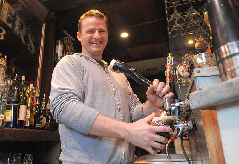 by: VERN UYETAKE - Mark Maher, brewmaster for Maher's Pub, gets in some beer pouring practice by pouring a Guinness for the St. Patrick's Day Festival that starts Thursday evening in Lake Oswego.