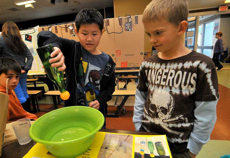 by: TIDINGS PHOTO: VERN UYETAKE - Wilfred Lim, on left, fifth grade, demonstrates how the force of the surface tension of the water in the bottle is stronger than that of the force of gravity exerted on the pingpong ball.