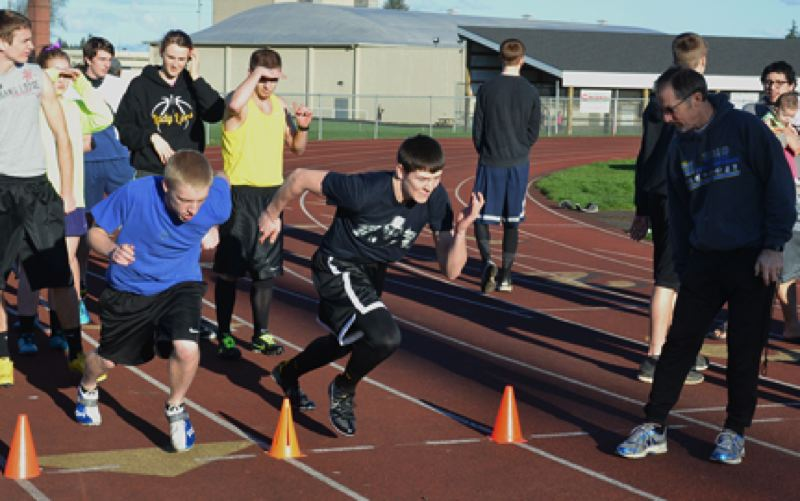 by: JOHN BREWINGTON - St. Helens sprinters Jeff Steinke (left) and Tanner Long line up for a 30-yard time trial during practice last week. Longtime Coach Gerry Tinkle was the starter. St Helens figures to be a young, but talented team this year.