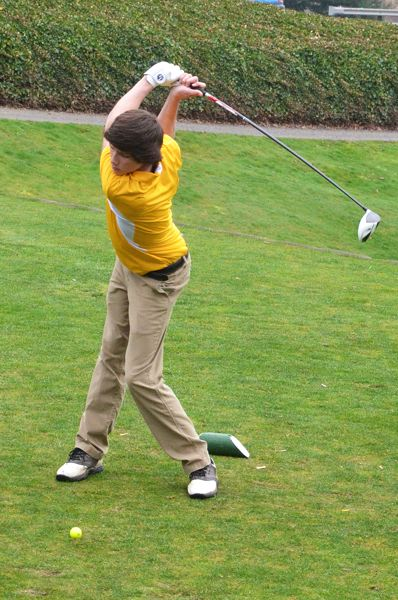 by: JOHN BREWINGTON - St. Helens' Jacob Roxey tees off in the first match of the season on Monday at the Wildwood Golf Course.