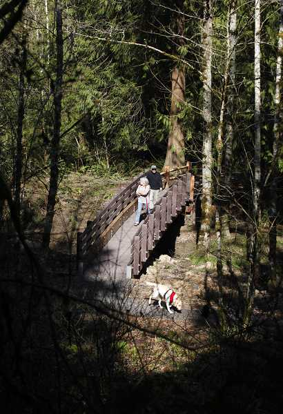 by: TIMES PHOTO: JONATHAN HOUSE - Will Bohnaker and Glenna Stater walk across a bridge and enjoy the creek's view in the new Jordan Woods Natural Area in Cedar Mill.