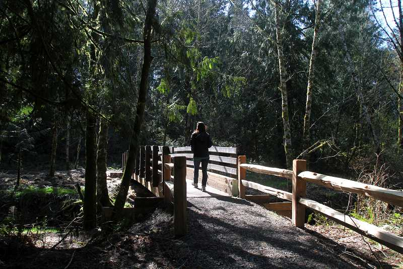 by: TIMES PHOTO: JONATHAN HOUSE - A woman walks across a bridge in the new Jordan Woods Natural Area.