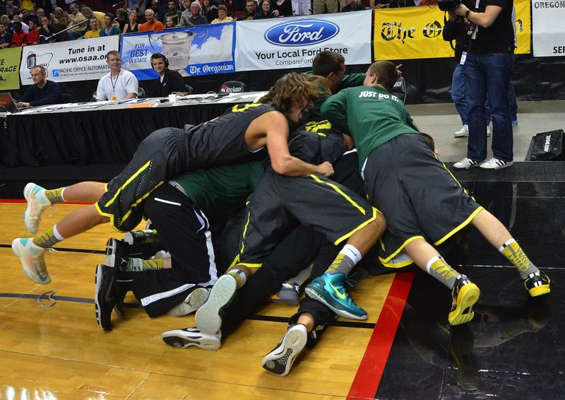 by: VERN UYETAKE - The West Linn boys basketball team storms the court in the moments following its victory over Central Catholic and the state title game on Saturday.