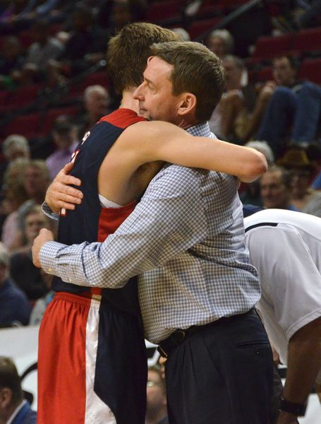 by: VERN UYETAKE - Lake Oswego coach Mark Shoff gives Calvin Hermanson a hug during the state tournament last week at the Rose Garden.