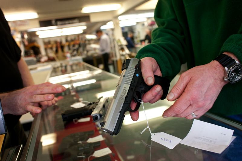 by: TRIBUNE PHOTO: CHRISTOPHER ONSTOTT - Don Evans shows a customer a handgun at the Northwest Armory gun shop in Southeast Portland. If adopted, House Bill 3200 would outlaw nearly all the most common pistols, rifles and shotguns owned by Oregonians by classifying them as 'assault weapons.'