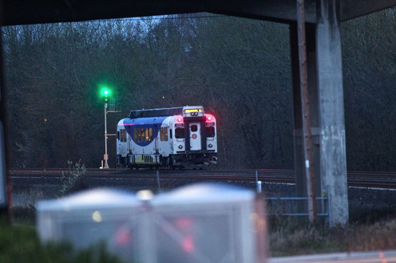 by: JAIME VALDEZ - A TriMet WES Commuter Rail train departs the scene of an investigation of an apparent suicide involving the the train below the 99W overpass in Tigard.