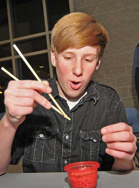 by: REVIEW PHOTO: VERN UYETAKE - Lakeridge High School freshman Trent Cowden of the Chinese Club tests his ability to use chopsticks by picking up pea seeds.