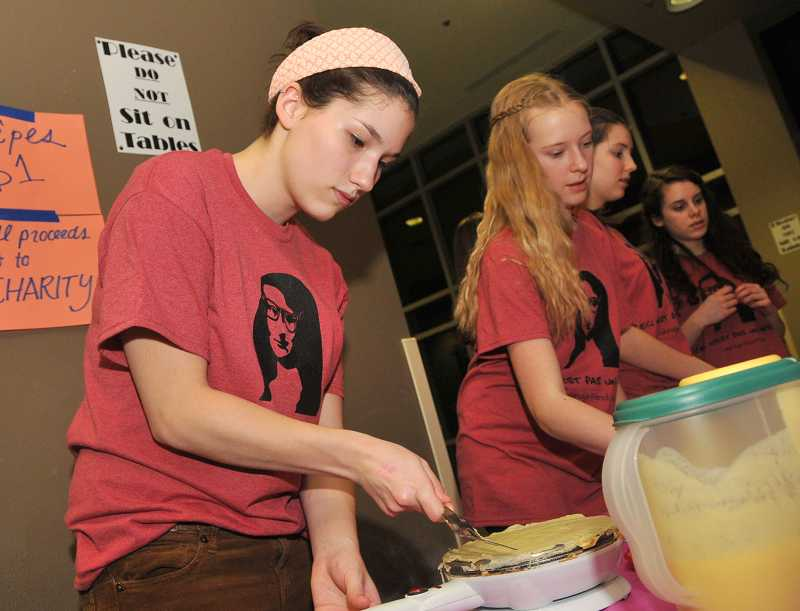 by: REVIEW PHOTO: VERN UYETAKE - Lakeridge High School senior Becca Duncan of the French Club prepares a crepe.