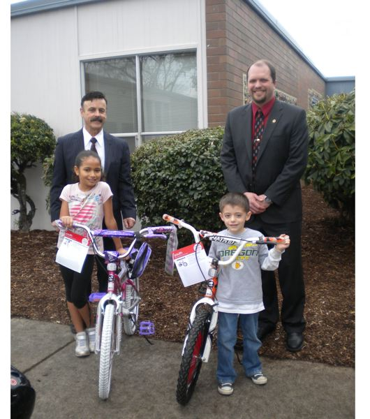 by: SUBMITTED PHOTO - Mike Churchill, left, and Jeff Schatz, Oregon City Masons from Multnomah Lodge #1, presented bikes to Takui Athena Katoanga and Andrew Cristofaro at Gaffney Lane Elementary School on March 1.