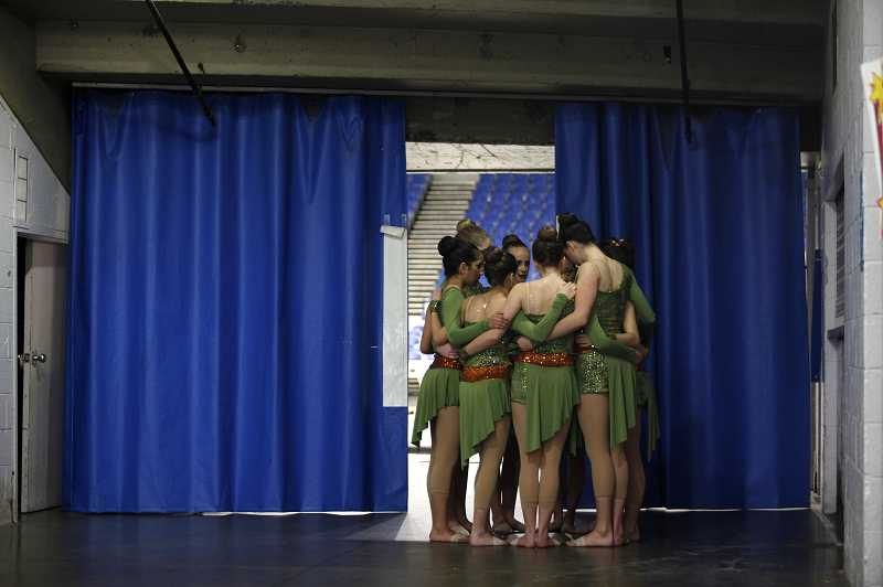 by: TIMES PHOTO: JONATHAN HOUSE - Valley Catholic's Charisma dancers huddle together for inspiration right before appearing on stage.